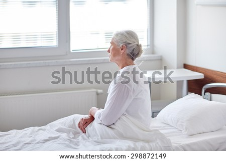 medicine, age, health care and people concept - senior woman patient lying in bed at hospital ward - stock photo