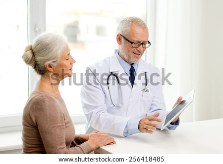 medicine, age, health care and people concept - smiling senior woman and doctor with tablet pc computer meeting in medical office - stock photo
