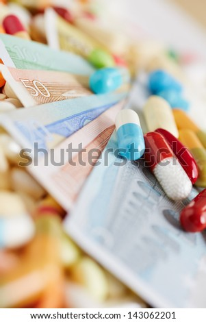 Medicine and Euro money bills with colorful different medication - stock photo