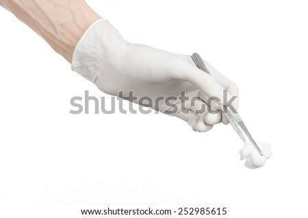 Medicine and Surgery theme: doctor's hand in a white glove holding tweezers with swab isolated on white background in studio