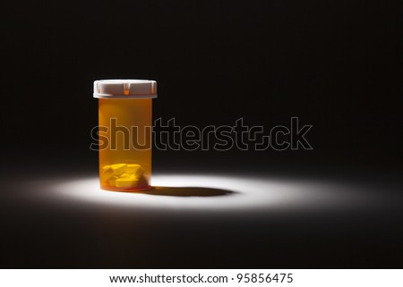 Medicine Bottle and Pills Under Spot Light Abstract. - stock photo