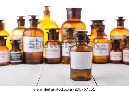 medicine bottle with blank label on wooden table - stock photo