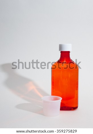 Medicine bottle with measuring cup on white background with shadow - stock photo