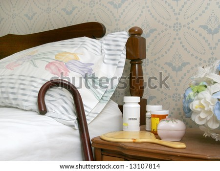 medicine bottles and a cane against a bed for an elderly person - stock photo