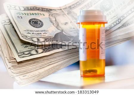Medicine bottles and a stack of twenty dollar bills with white vignette - stock photo
