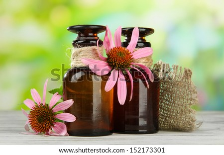 Medicine bottles with purple echinacea flowers on wooden table, outdoors - stock photo