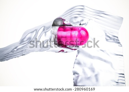 Medicine capsule in torn packaging on light background. Toned. - stock photo