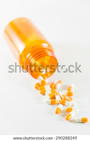 medicine capsule spilling out of a bottle