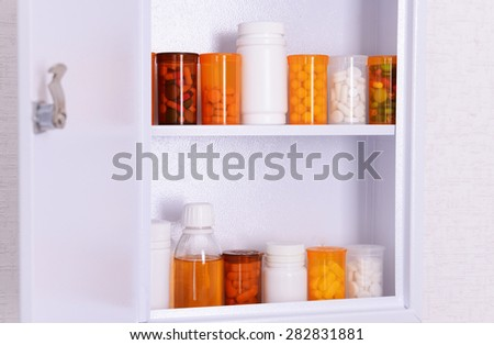 Medicine chest with bottles of pills, closeup