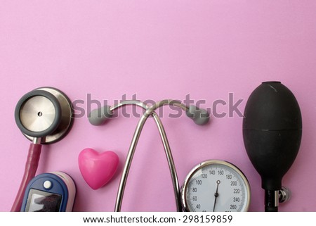 Medicine concept - stethoscope, blood pressure equipment, heart and pulse oximetere on pink background - stock photo