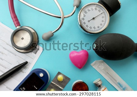 Medicine concept - stethoscope, pills, blood pressure equipment, pulse oximeter, sterile gloves, needle, heart, recipes and bottles on blue background - stock photo