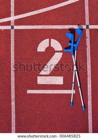 Medicine crutch. Number two. Big white track number on red rubber racetrack. Gentle textured running racetracks in athletic stadium. - stock photo