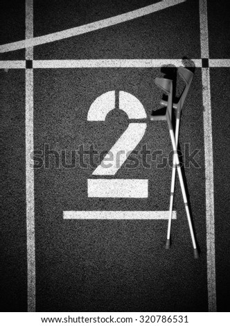 Medicine crutch. Number two. Big white track number on rubber racetrack. Gentle textured running racetracks in athletic stadium. . Black and white photo - stock photo