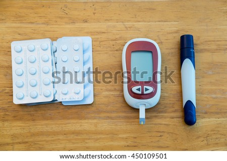 Medicine, diabetes, glycemia, health care and people concept -  Blood Glucose meter, lancelet and pile of pills in blister packs - stock photo