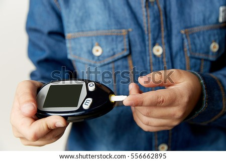 medicine, diabetes, glycemia, health care and people concept - close up of man checking blood sugar level by glucometer  test stripe at home
