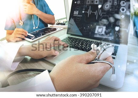 Medicine doctor hand working with modern computer and digital pro tablet with his team with  diagram on wooden desk as medical concept