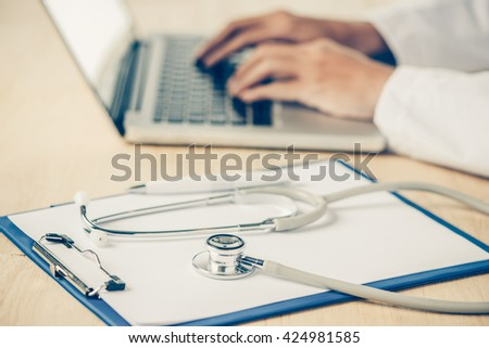 Medicine doctor hand working with modern computer and smart phone on wooden desk as medical concept - stock photo