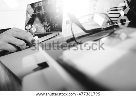 Medicine doctor hand working with modern digital tablet and laptop  with computer interface as medical network concept, black white