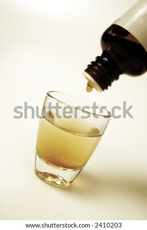 Medicine dropping in a small glass of water - stock photo