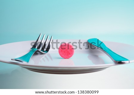 Medicine for digestion concept with plate with big red tablet and for and table knife - stock photo