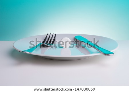 Medicine for digestion concept with plate with big white tablet and for and table knife - stock photo