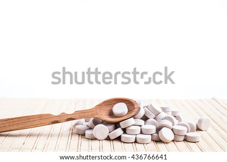 Medicine green and yellow pills or capsules on wooden background with copy space. Drug prescription for treatment medication. Pharmaceutical medicament, cure in container for health. Antibiotic - stock photo
