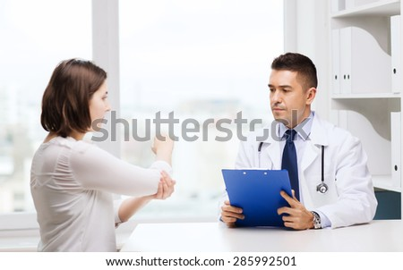 medicine, health care and people concept - young woman showing elbow to doctor with clipboard and meeting at hospital