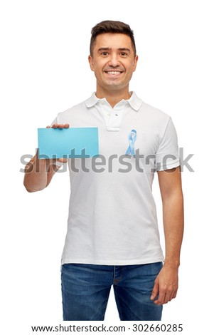 medicine, health care, gesture and people concept - middle aged latin man in t-shirt with sky blue prostate cancer awareness ribbon holding blank paper card - stock photo