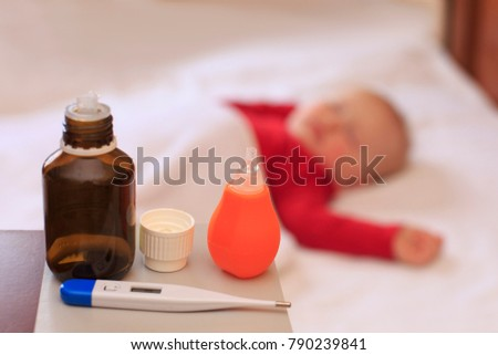 Medicine on the table, in the background sick little girl is lying on bed
