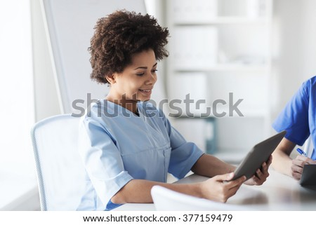medicine, people and healthcare concept - happy female doctor or nurse with tablet pc computer at hospital - stock photo