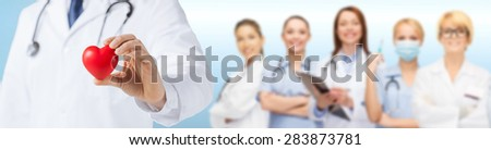 medicine, people, charity, health care and cardiology concept - close up of male doctor hand holding red heart over medical team - stock photo