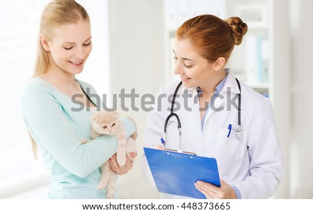 medicine, pet, animals, health care and people concept - happy woman holding scottish fold kitten and veterinarian doctor with clipboard at vet clinic - stock photo