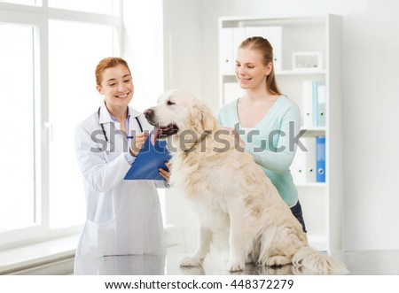 medicine, pet, animals, health care and people concept - happy woman with golden retriever dog and veterinarian doctor writing to clipboard at vet clinic - stock photo
