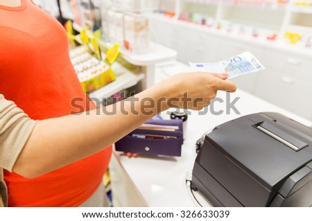 medicine, pharmaceutics, health care and people concept - close up of pregnant woman giving money and buying medication at cash register in drugstore - stock photo
