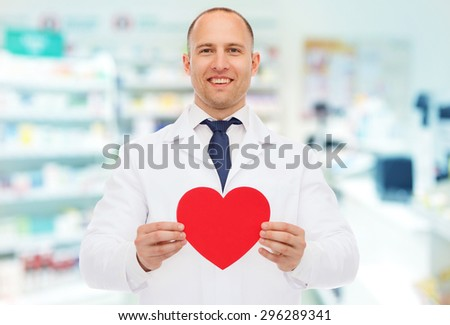 medicine, pharmacy, people, health care and pharmacology concept - happy male pharmacist holding red heart shape over drugstore background - stock photo
