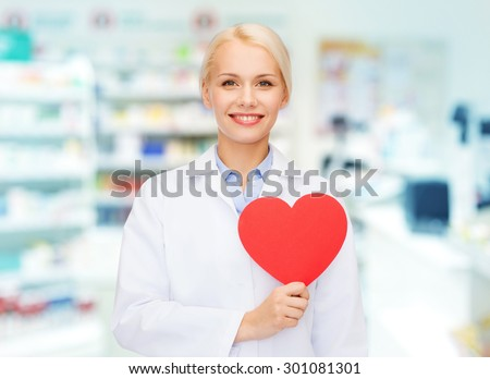 medicine, pharmacy, people, health care and pharmacology concept - happy young woman pharmacist holding red heart shape over drugstore background - stock photo