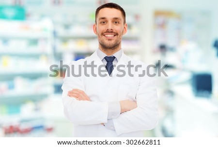 medicine, pharmacy, people, health care and pharmacology concept - smiling male pharmacist in white coat over drugstore background - stock photo