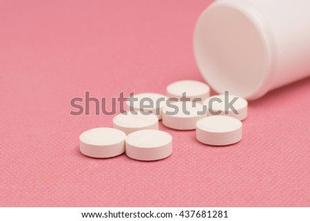 Medicine pills and bottle on pink background. Selective focusing. - stock photo