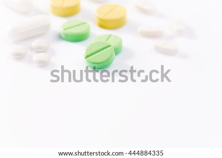 Medicine pills in various shapes, colors, and sizes on white background with selective focus on the front green pill, back lighting to create hard long shadows, copyspace for text at bottom of frame  - stock photo