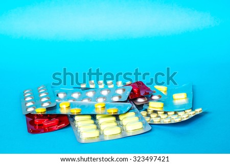 Medicine pills or capsules with copy space and pink sheet on blue background. Drug prescription for treatment medication. Pharmaceutical medicament, cure in container for health. - stock photo