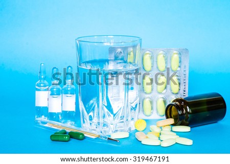 Medicine pills or capsules with glass of water and thermometer on blue background. Drug prescription for treatment medication. Pharmaceutical medicament, cure in container for health.  - stock photo