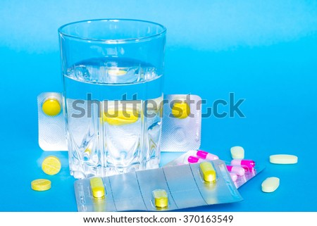 Medicine pills or capsules with glass of water on blue background. Drug prescription for treatment medication. Pharmaceutical medicament, cure in container for health.  - stock photo