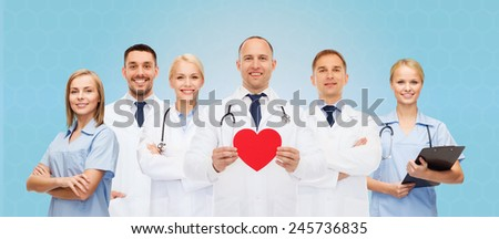 medicine, profession, teamwork and healthcare concept - group of smiling medics or doctors holding red paper heart shape, clipboard and stethoscopes over blue background - stock photo