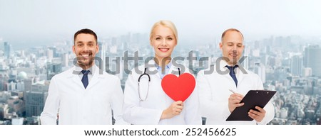 medicine, profession, teamwork and healthcare concept - group of smiling medics or doctors holding red paper heart shape, clipboard and stethoscopes over city background - stock photo