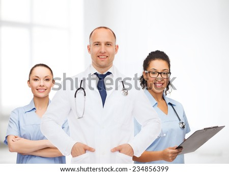 medicine, profession, teamwork and healthcare concept - international group of smiling medics or doctors with clipboard and stethoscopes over hospital background - stock photo