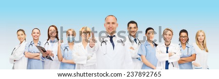 medicine, profession, teamwork and healthcare concept - international group of smiling medics or doctors with clipboard and stethoscopes with showing thumbs up over blue background