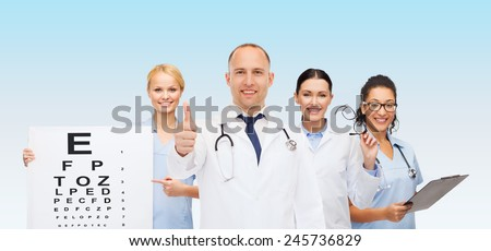 medicine, profession, teamwork and healthcare concept - international group of smiling medics or doctors with eye chart, clipboard and stethoscopes over blue background - stock photo