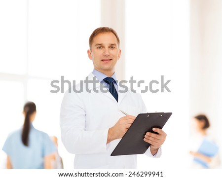 medicine, profession, teamwork and healthcare concept - smiling male doctor with clipboard writing prescription over group of medics - stock photo