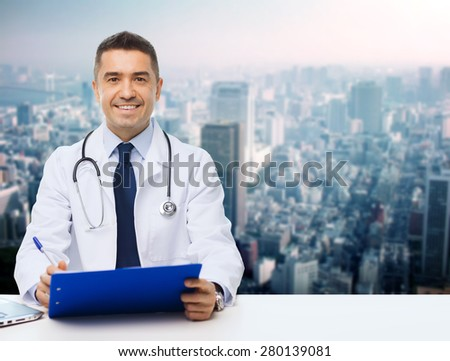medicine, profession, technology and people concept - happy male doctor with clipboard and stethoscope over city background - stock photo