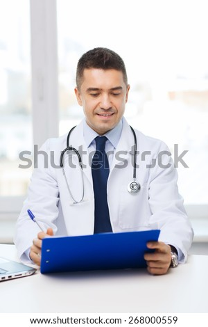 medicine, profession, technology and people concept - happy male doctor with clipboard in medical office - stock photo